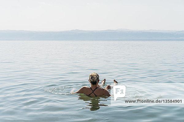 Woman floating  swimming in Dead Sea  Jordan