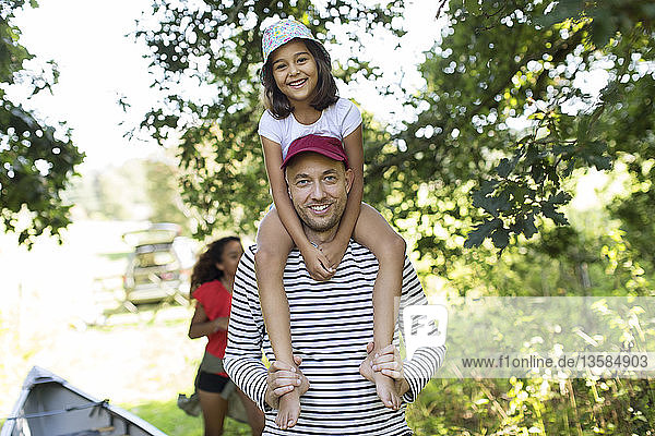 Portrait father carrying daughter on shoulders in woods