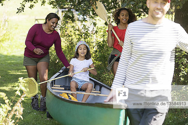Family carrying canoe in woods