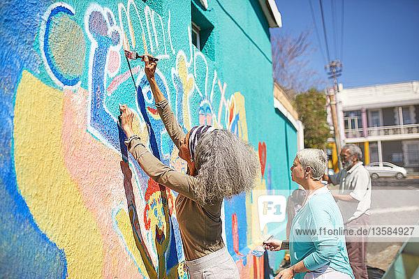 Senior community volunteers painting vibrant mural on sunny urban wall