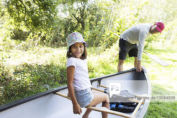 Father and daughter with canoe in woods