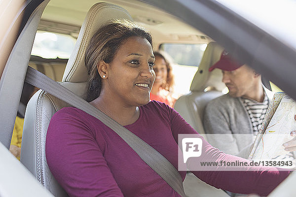 Smiling woman driving car with family on road trip