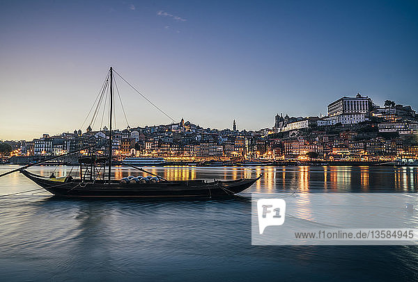 Waterfront city behind moored ship at night  Porto  Portugal