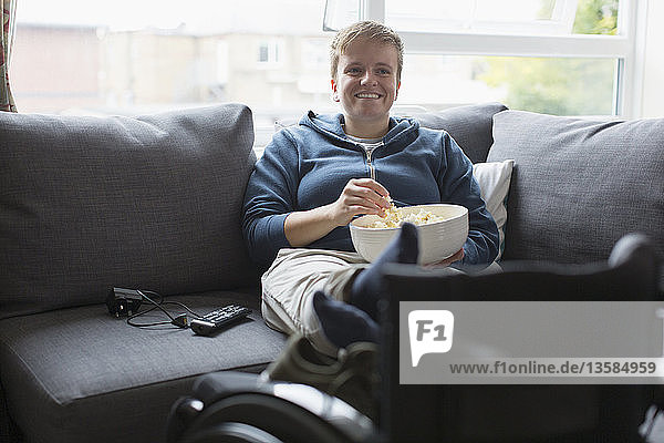 Smiling young woman watching TV and eating popcorn on sofa with feet up on wheelchair
