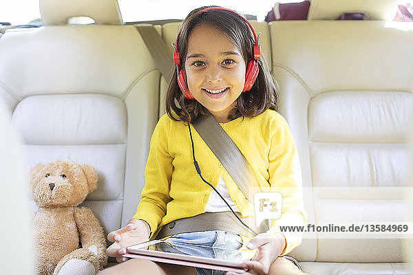 Portrait smiling  confident girl watching movie with headphones and digital tablet in back seat of car