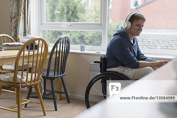Young woman in wheelchair listening to music with headphones at window