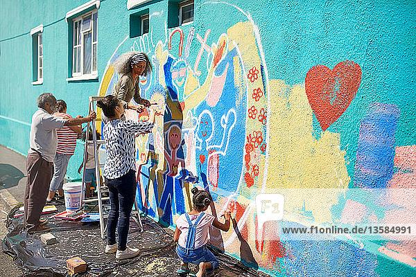 Community volunteers painting multicolor mural on sunny urban wall
