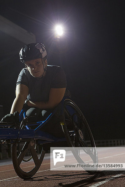 Portrait determined young female paraplegic athlete training for wheelchair race on sports track at night