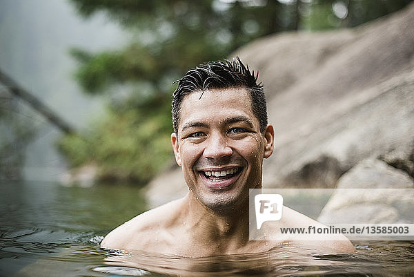Portrait smiling  handsome young man swimming in lake