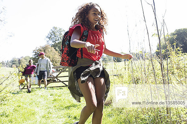 Happy girl with backpack camping  running in sunny field