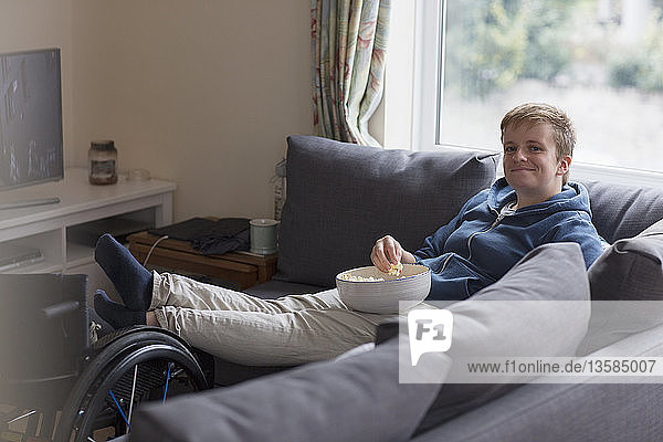 Portrait confident young woman watching TV and eating popcorn on sofa with feet up on wheelchair