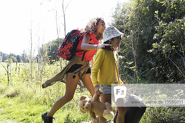 Sisters camping  carrying suitcase and teddy bear in sunny field