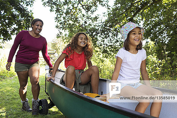Happy mother and daughters pushing canoe in woods