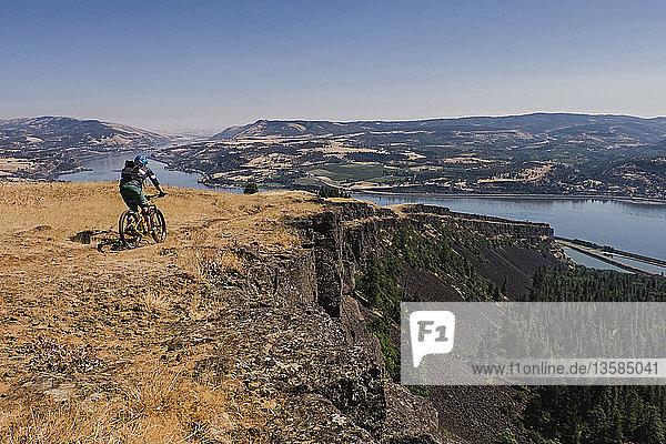 Man mountain biking on cliff along Columbia River  Hood River  Oregon  USA