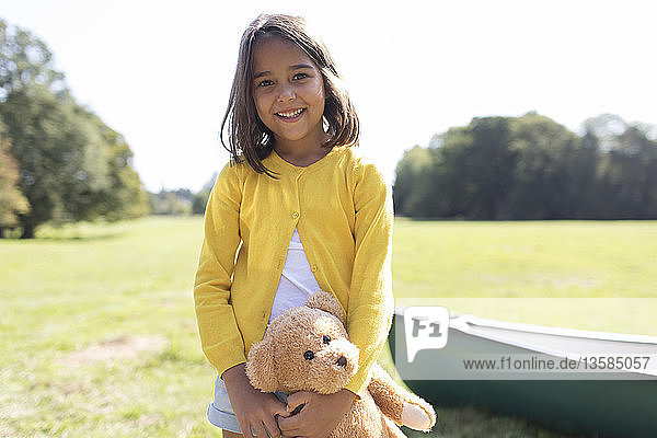 Portrait smiling  cute girl with teddy bear in sunny field