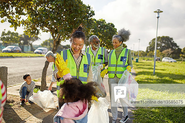 Happy volunteers high-fiving  cleaning up litter in sunny park