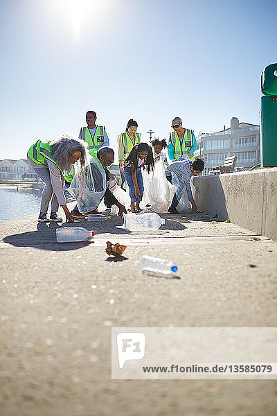 Volunteers picking up plastic litter on sunny boardwalk