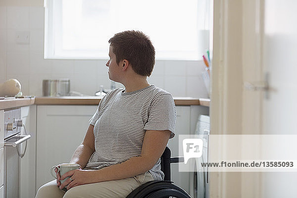 Thoughtful young woman in wheelchair drinking tea in apartment kitchen