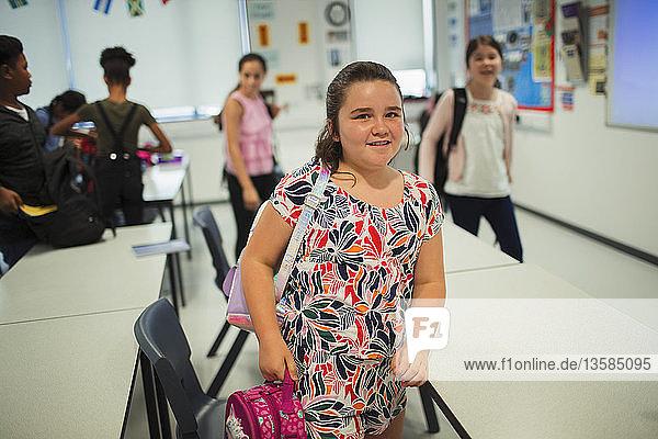 Portrait confident junior high school girl student leaving classroom