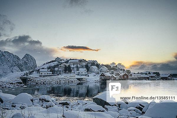 Tranquil snow covered waterfront fishing village  Reine  Lofoten Islands  Norway
