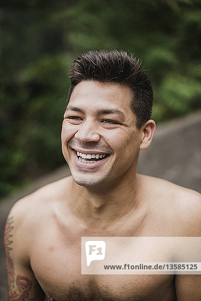 Portrait happy  handsome bare chested man laughing