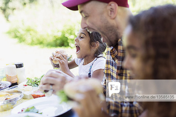 Playful father and daughter eating barbecue hamburgers at campsite