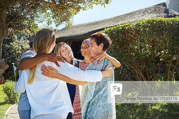 Happy women friends hugging in circle
