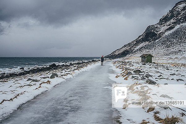 Woman walking along icy beach,  Lofoten Islands,  Norway