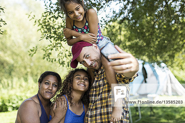 Happy  affectionate family taking selfie with camera phone at campsite