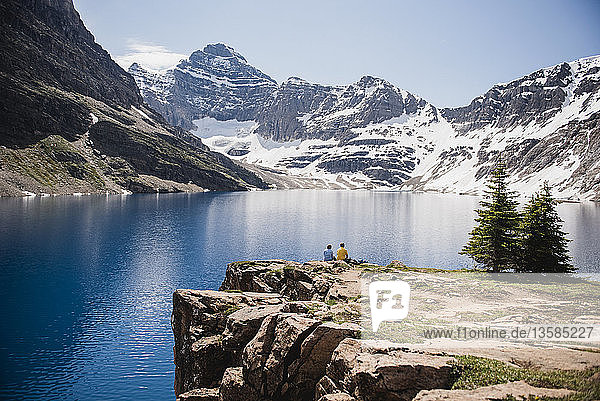 Couple sitting on cliff overlooking tranquil  sunny mountains and lake  Yoho Park  British Columbia  Canada
