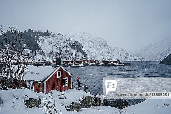 Woman enjoying tranquil snowy mountain view from waterfront fishing village  Lofoten Islands  Norway