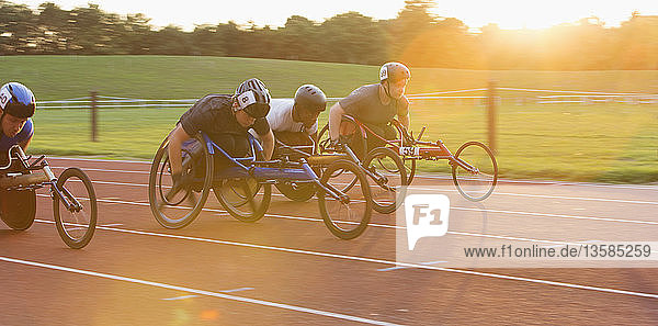 Determined paraplegic athletes speeding along sports track in wheelchair race