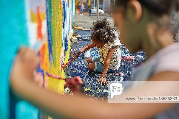 Girls painting mural on wall