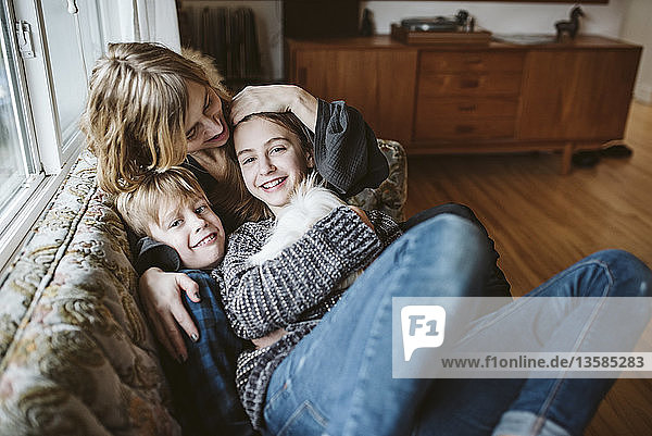 Portrait affectionate mother and children with guinea pig on living room sofa