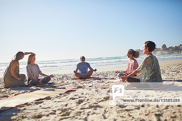 Group meditating on sunny beach during yoga retreat