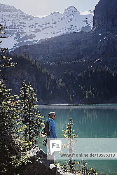 Female hiker looking at sunny  idyllic mountain lake view  Yoho Park  British Columbia  Canada