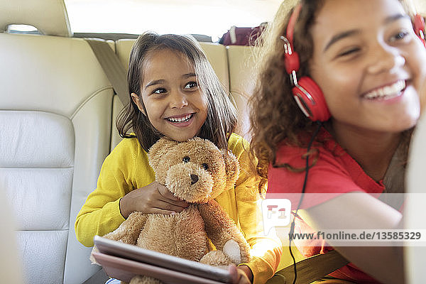 Happy sisters with teddy bear riding in back seat of car