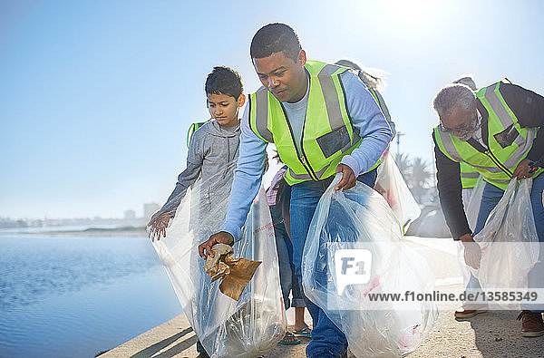 Multi-generation family men volunteering  picking up litter on waterfront pier