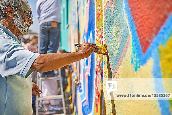 Senior man painting mural on sunny wall