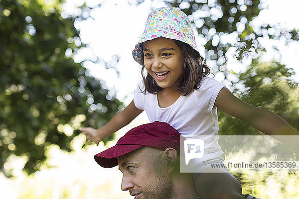 Happy  carefree girl on father's shoulders