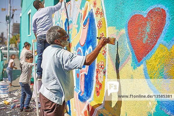 Senior man painting mural on sunny urban wall