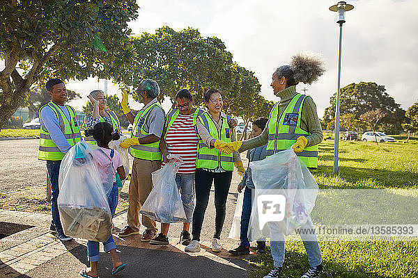 Happy volunteers celebrating  cleaning litter from sunny park