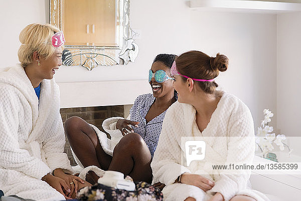 Young women friends wearing eye masks in bedroom