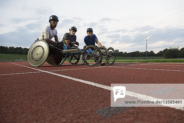 Portrait determined paraplegic athletes training for wheelchair race on sports track