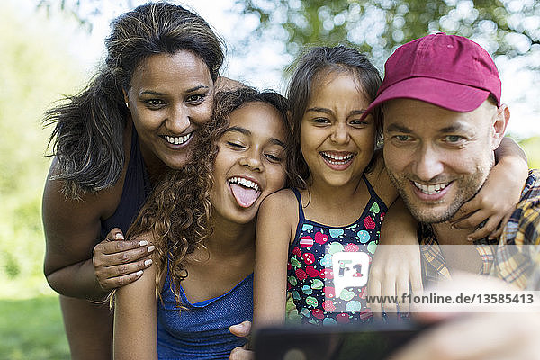 Playful family taking selfie with camera phone