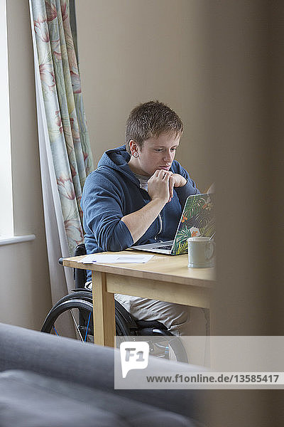 Focused young woman in wheelchair using laptop at dining table
