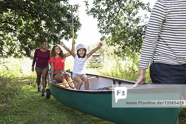 Excited family carrying canoe in woods