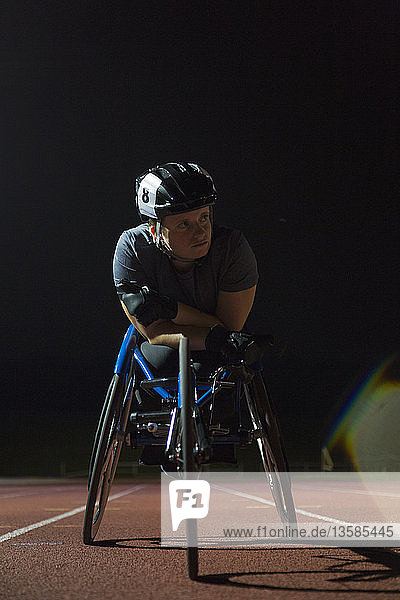 Determined young female paraplegic athlete training for wheelchair race on sports track at night