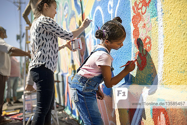 Girl volunteer painting vibrant mural on sunny wall