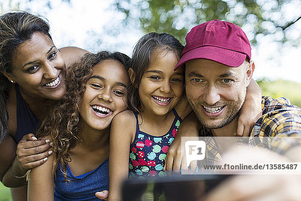 Happy family taking selfie with camera phone